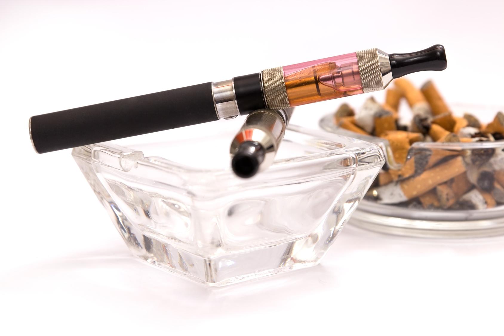 E-Zigarette in Aschenbecher und voller Aschenbecher mit Tabakzigaretten im Hintergrund